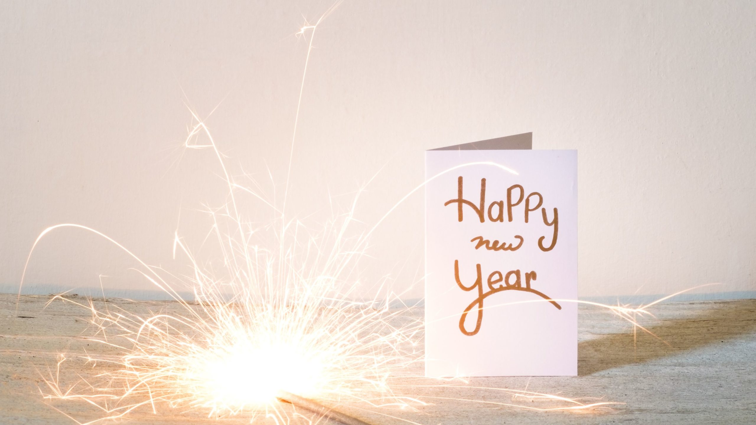 new-year-card-with-lit-sparkler-on-table-against-wall-688969401-5bd668bc46e0fb0026718605